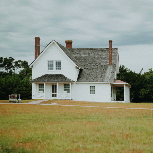 A white detached house in the middle of a field